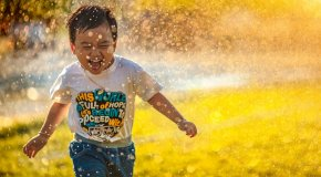 boy playing in sprinklers